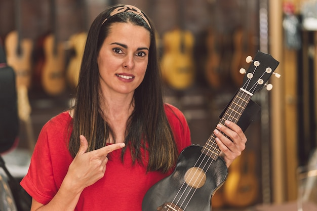 Portrait of a woman showing a small-sized classical guitar in a instruments store