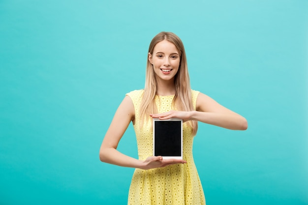 Portrait woman showing tablet computer screen smiling wearing yellow dress isolated on blue background.