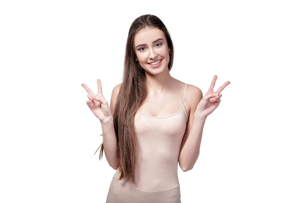 Portrait of woman showing two fingers or victory gesture isolated on white background.