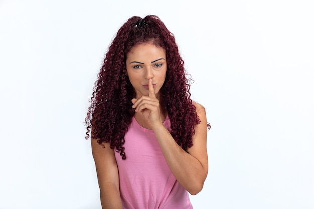 Portrait of a woman signaling silence with her index finger in front of her lips. isolated on a white background.