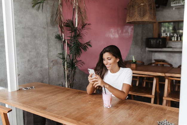 Portrait of woman sitting in cafe and chatting with smile in smartphone
