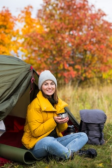 Portrait of woman sitting near green tent and drinking tea or coffee in autumn forest