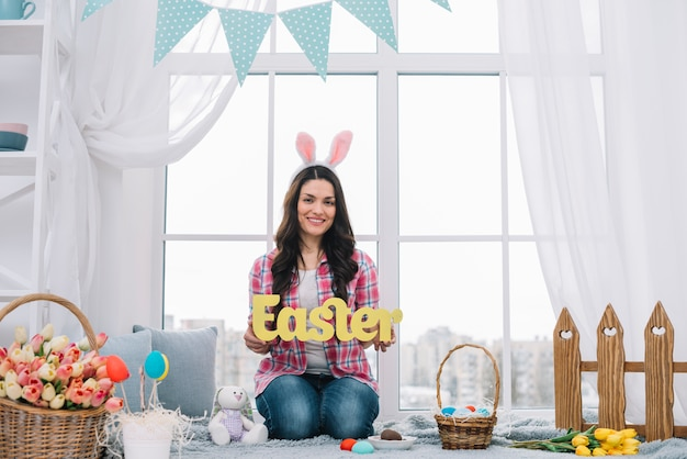 Portrait of a woman sitting near the window showing yellow easter word