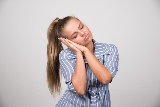 Ritratto di donna che dorme sul muro grigio.