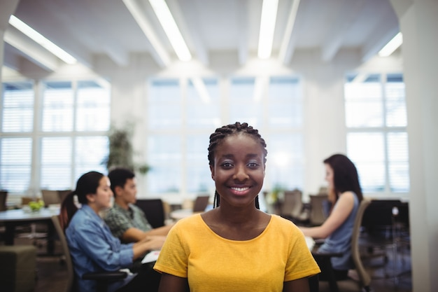 Portrait of woman smiling at camera while colleagues working in