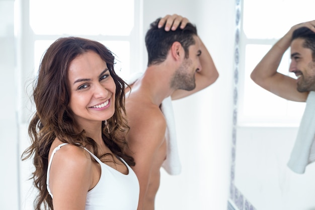 Portrait of woman smiling while man looking in mirror
