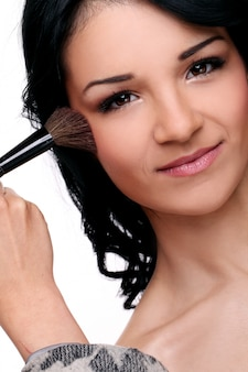 Portrait of woman smiling while someone makes up her