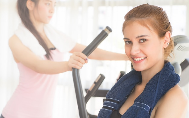 Portrait of a woman in sportwear and towel training with friend
