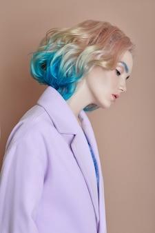 세로 여자 봄 밝은 색의 비행 머리, 모든 음영 보라색 파란색. 헤어 컬러링, 아름다운 입술과 메이크업. 바람에 펄럭이는 머리카락. 섹시한 여자 코트 짧은 머리. 전문적인 크리에이티브 컬러링