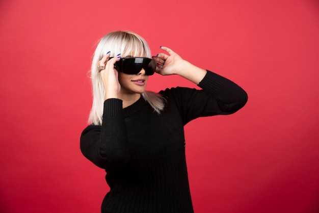 Portrait of woman standing and posing with a black glasses on a red wall.