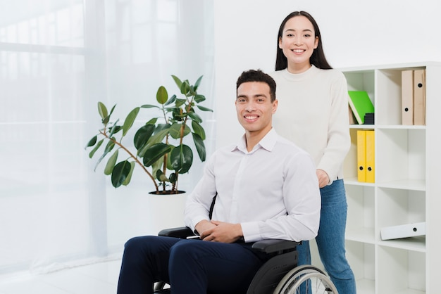 Portrait of a woman standing behind the smiling businessman sitting on wheelchair