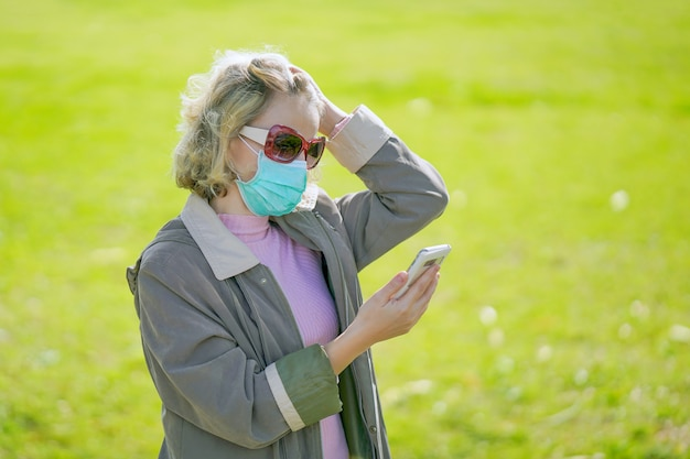 Portrait of woman on the street in a medical mask and speaks on the phone. attractive unhappy model with flu outdoors.