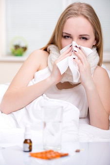 Portrait of woman suffering from cold in bed.