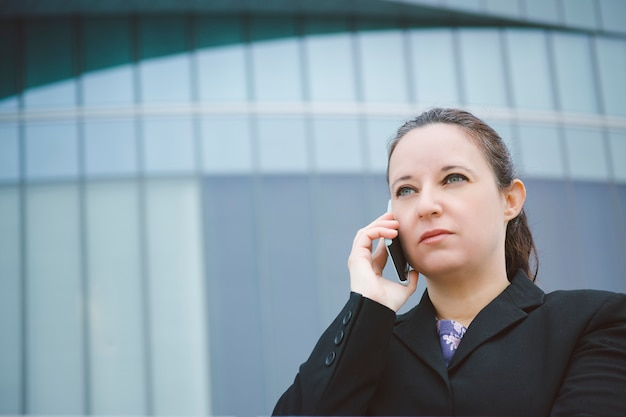 Portrait of a woman in a suit talking on a serious phone