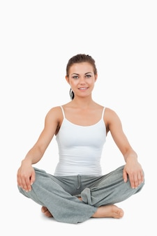 Portrait of a woman in the sukhasana position against a white background