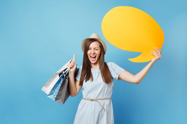 Portrait of woman in summer dress, straw hat holding packages bags with purchases after shopping, empty blank say cloud, speech bubble card isolated on blue pastel background. copy space advertisement
