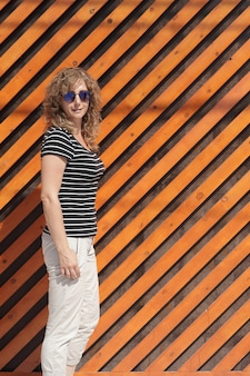 Portrait of a woman in sunglasses against the background of an orange striped wall