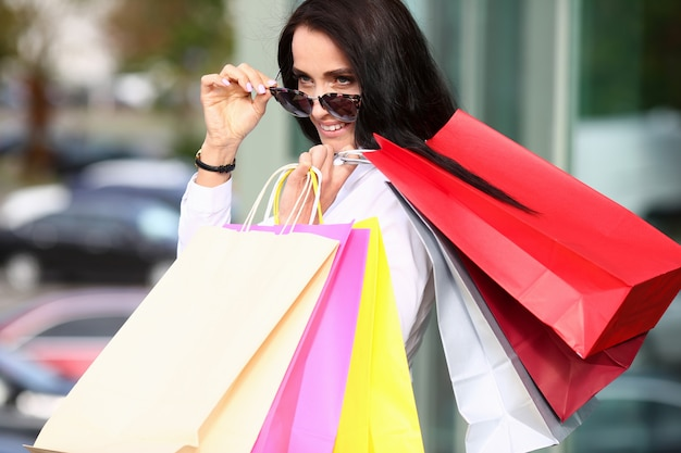 Portrait woman in sunglasses holding multicolored paper bags in hands.