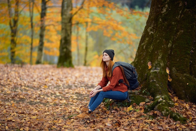 Portrait of a woman in a sweater and jeans and a hat under a tree in the autumn forest
