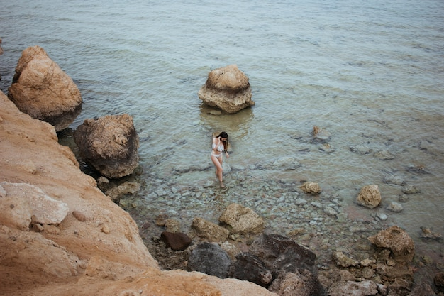 Portrait of woman in a swimsuit of european appearance walks along the shores of the red sea in egypt, rocky landscape.
