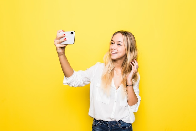 Il ritratto della donna prende selfie che tiene il telefono astuto in mano che spara selfie isolato sulla parete gialla