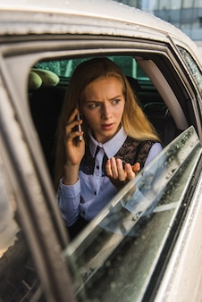 Portrait of woman talk by cellphone, sits in car