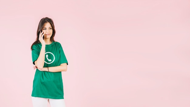 Portrait of a woman talking on cellphone wearing whatsapp icon t-shirt