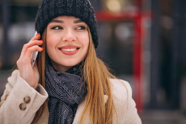 Portrait of woman talking on phone in the street
