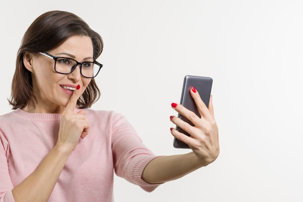 Portrait of woman tells secrets and gossip on cell phone