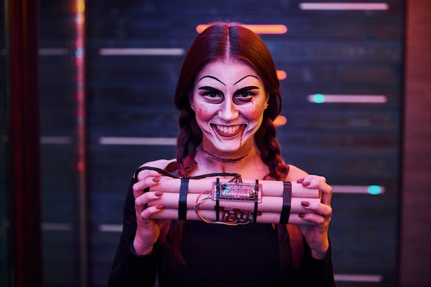 Portrait of woman that is on the thematic halloween party in scary makeup and costume with bomb in hands.