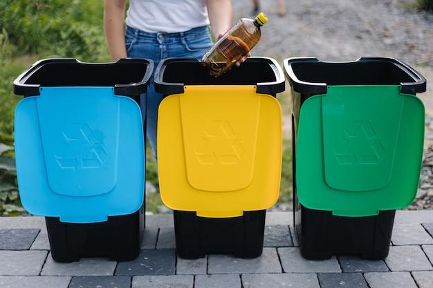 Портрет женщины, бросающей пустую пластиковую бутылку из-под воды в мусорное ведро, дерево для мусора на открытом воздухе