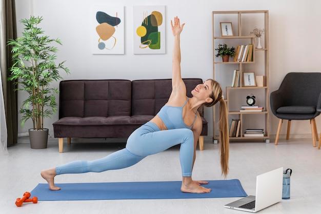 マットの上で自宅でトレーニングする肖像画の女性
