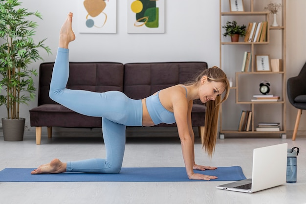 Portrait woman training at home on mat