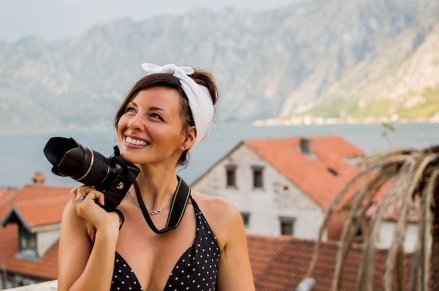 Portrait of woman traveler photography outside surrounded with mountains.