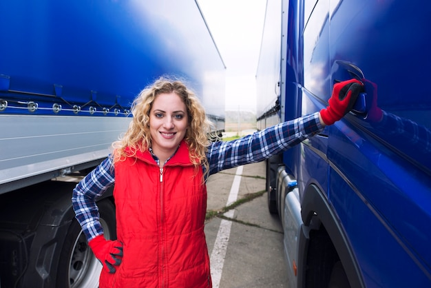Portrait of woman truck driver standing by truck vehicle