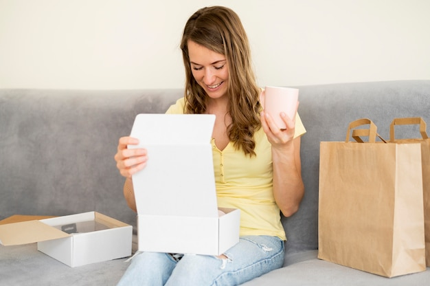 Portrait of woman unboxing products ordered