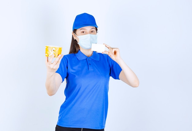 Portrait of woman in uniform and medical mask holding card