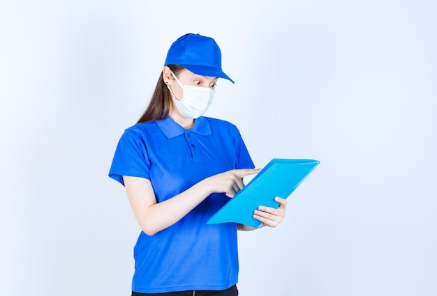Portrait of woman in uniform and medical mask holding folder
