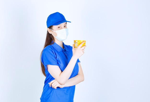 Portrait of woman in uniform and medical mask holding plastic cup Free Photo