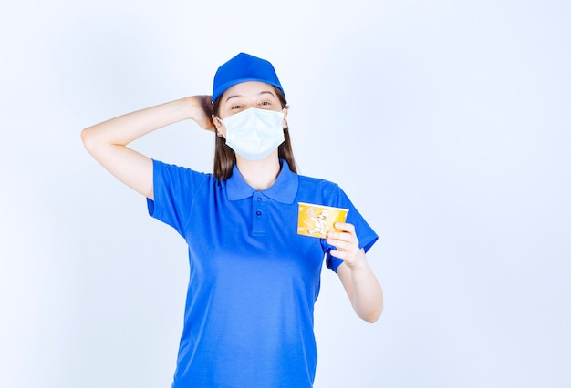 Portrait of woman in uniform and medical mask holding plastic cup