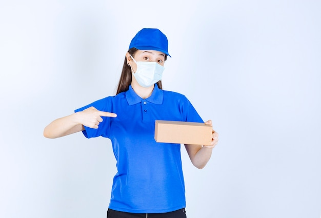Portrait of woman in uniform and medical mask pointing at paper box