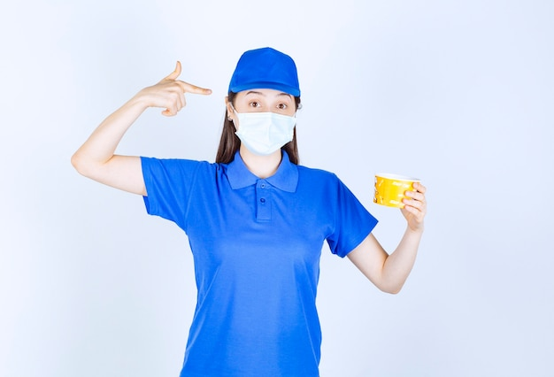 Portrait of woman in uniform and medical mask pointing at plastic cup