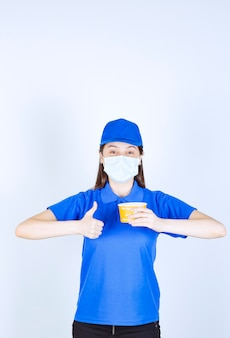 Portrait of woman in uniform and medical mask with plastic cup showing thumb up