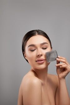 Portrait of woman using facial oil blotting paper on grey background