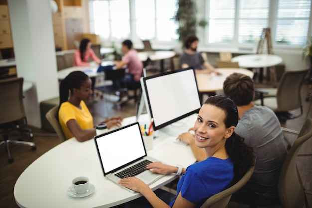 Portrait of woman using laptop at her desk
