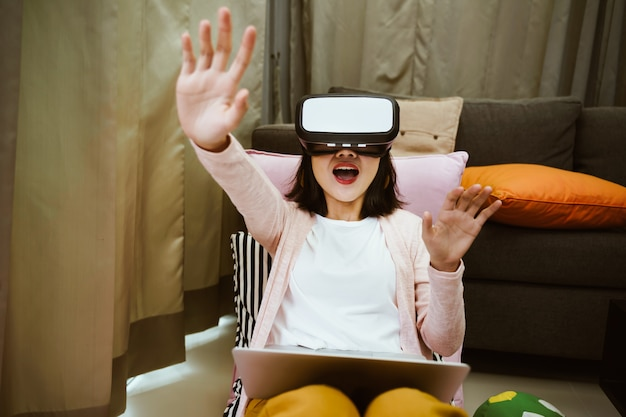 Portrait of woman using virtual reality glasses with exciting at home