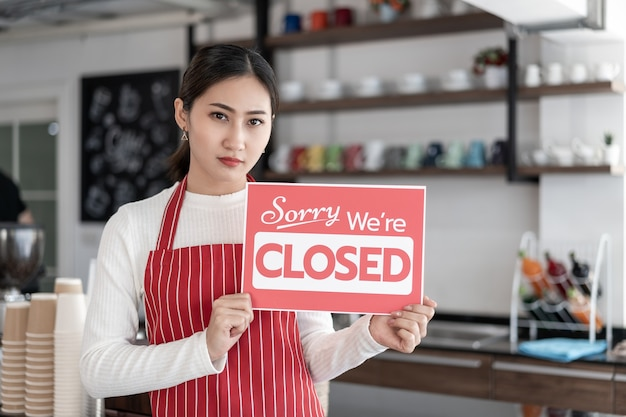 Portrait of woman waitress standing at her coffee shop gate with showing closed signboard