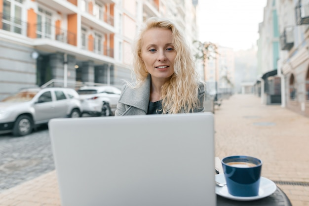 Portrait of woman in warm in an outdoor cafe with laptop
