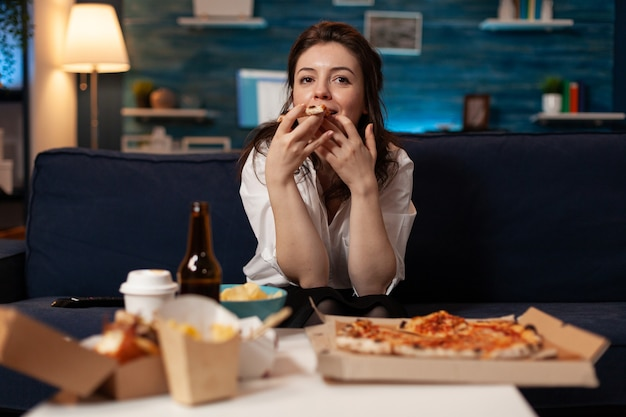 Portrait of woman watching comedy movie eating tasty delivery pizza slice relaxing on sofa