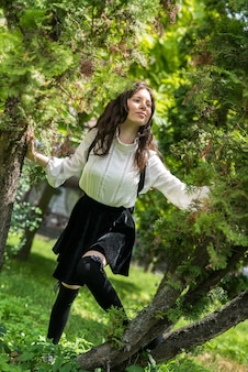 Portrait of a woman wear white blouse and stylish black skirt near green tree, city park
